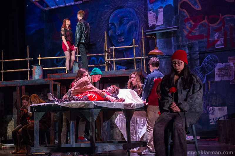 "Pioneer Theatre Guild: Rent | The white flowers held by cast members in ""Seasons of Love B"" are now red in ""Without You,"" as Angel (Robbie Stephens) is surrounded by his friends in his last hours of life."
