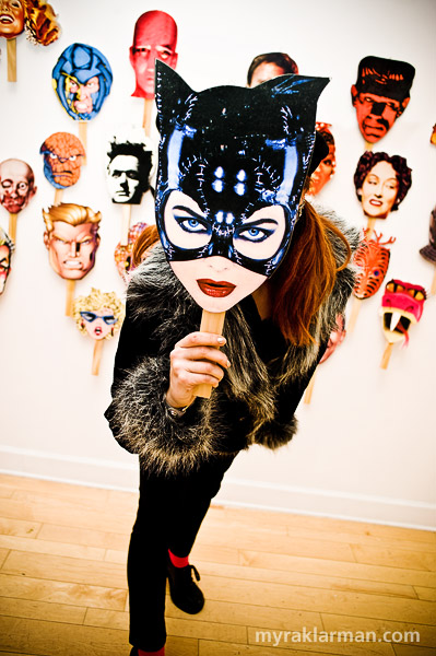 Gallery Project: Step Right Up! | Nina Friday plays with one of the masks in Jack Summers's installation.
