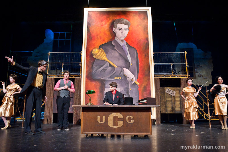 Pioneer Theatre Guild: Urinetown | The office of Caldwell B. Cladwell, the money-grubbing, cold-hearted, Hobbesian president and owner of Urine Good Company (UGC on the NASDAQ). Cladwell's portrait was expertly painted by Raye Evrard and Elayne Fivenson, with David Zinn.