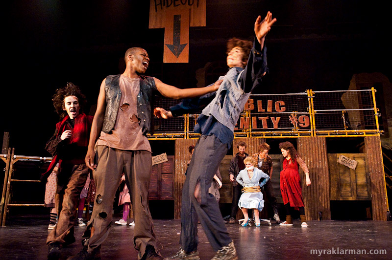 "Pioneer Theatre Guild: Urinetown | Hot Blades Harry (John Spalding), center, shows Tiny Tom (Russel Norris) the meaning of ""Urinetown"" in What is Urinetown? I love the enormous sign (partially visible in the photo) that reads ""Secret Hideout"" — and even features a helpful arrow showing just where it is. This is typical of the self-referential (and in this instance, self-negating) humor of the show."