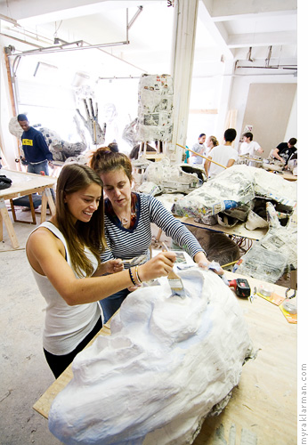 FestiFools April 1st Parade | U-M Scenic Painter Toni Auletti (right) works with U-M Freshman Rachel Orloff to paint one of the puppet heads.