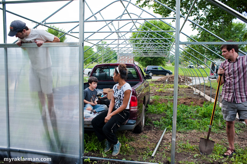 Hoop House Dreams | Shannon Brines (an extremely long-legged, Dexter-based hoop house farmer) admires one of the newly installed hard-plastic end walls.