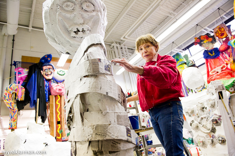Marching towards FestiFools 2010 | Community volunteer Joan French primes a puppet for its final layer of color.