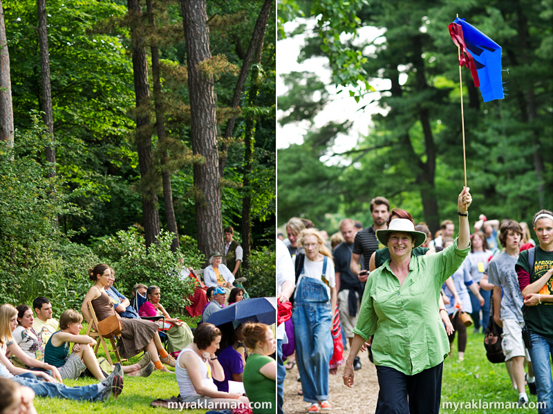 Shakespeare in the Arb: A Midsummer Night's Dream | The audience, seated on chairs and blankets, watches the action. During the performance I attended, umbrellas provided protection from both the sun and rain. | UM lecturer Kate Mendeloff not only has directed every Shakespeare in the Arb production, but with flag in hand, she also leads the audience to the various locations within the Arb where the action is staged.