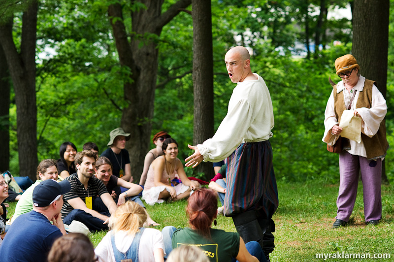 Shakespeare in the Arb: A Midsummer Night's Dream | In some scenes there is hardly a barrier between the actors and the audience. The story features a play within a play — here, the character Bottom (Sam Dodge) constantly interrupts director Peter Quince (Jane Glass) as he attempts to cast the play.